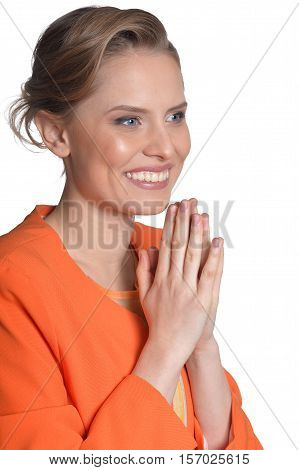 Portrait of cheerful young woman with clasped hands isolated on white background