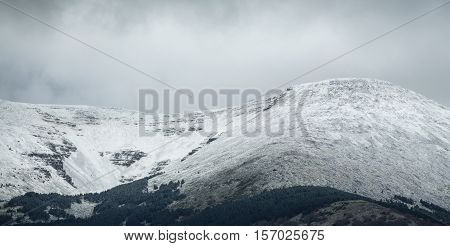 Clouds over Moncayo snowcapped summit in Moncayo Natural Park, Zaragoza, Spain