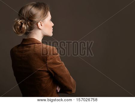 Side view of young woman with crossed arms against grey background