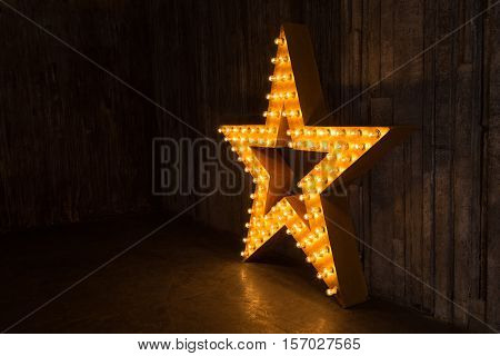Photo gold star with lights on the background of dark scenes