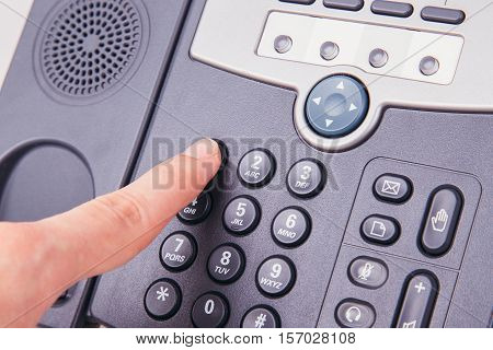 Finger pressing number button on telephone to make a call close up