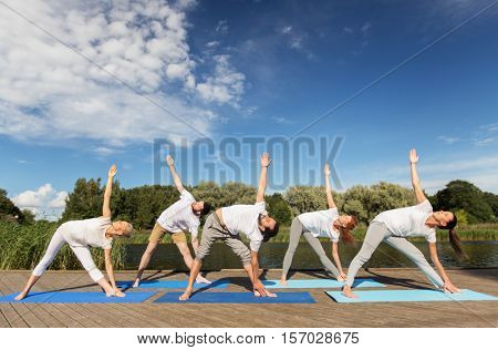 fitness, sport, and healthy lifestyle concept - group of people making left triangle pose on mat outdoors on river or lake berth