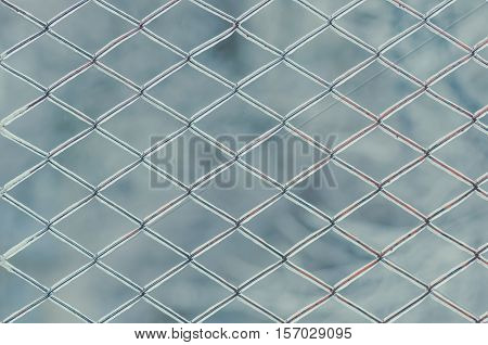 Metal grid in ice. In winter the rain and froze on the fence mesh. Background.
