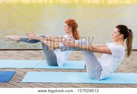 fitness, sport, yoga, people and healthy lifestyle concept - women making half-boat pose on mat outdoors on river or lake berth