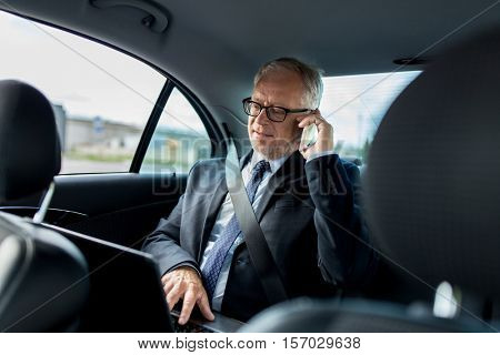 transport, business trip, technology and people concept - senior businessman with laptop computer calling on smartphone and driving on car back seat