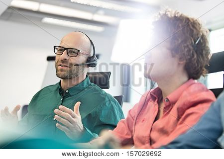 Mid adult businessman talking on headset with male colleagues in foreground at office