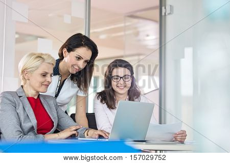 Team of businesswomen using laptop at table in office