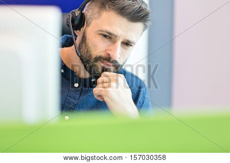 Thoughtful mid adult businessman wearing headset at office