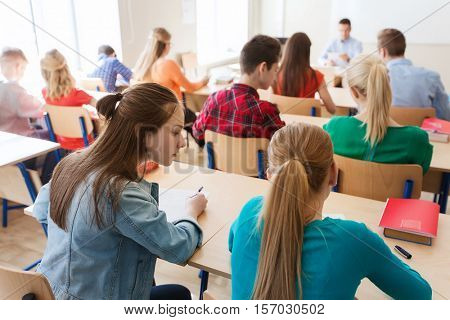 education, learning, cheating and people concept - group of students writing school test