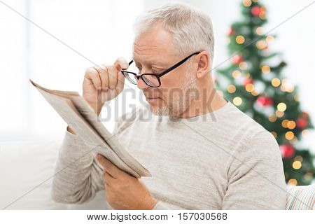 holidays, information, people, vision and mass media concept - senior man in glasses reading newspaper at home over christmas tree background