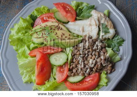 Healthy green salad with boiled cod fish lentils tahini parsley tomatoes cucumbers avocados flax seeds on a large gray plate. Love for a healthy raw food concept