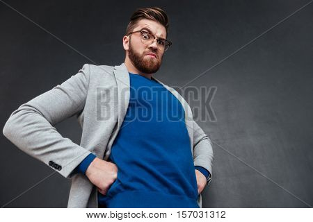 Angry bearded young businessman in glasses standing with hands on hips