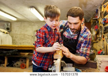 family, carpentry, woodwork and people concept - father and little son with plane working with wood plank at workshop
