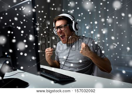 technology, gaming, entertainment, let's play and people concept - man in eyeglasses with headset playing and winning computer game at home and streaming playthrough or walkthrough video over snow