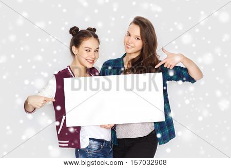 winter, christmas, people, advertisement and holidays concept - happy smiling pretty teenage girls or friends holding and pointing finger to white blank board over gray background and snow