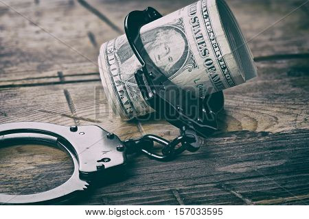 Handcuffs And Money On Wooden Table