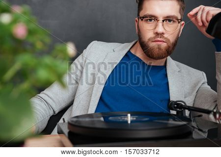 Confident bearded young businessman in glasses with turntable