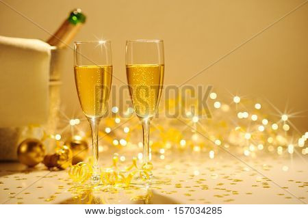 Champagne Flutes On Table Decorated With Streamer And Gold Confetti.
