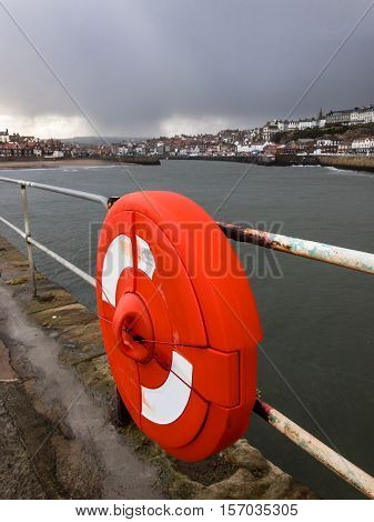 WHITBY ENGLAND - NOVEMBER 5: Life preserver ring and a storm approaching Whitby. In Whitby North Yorkshire England. On 5th November 2016.