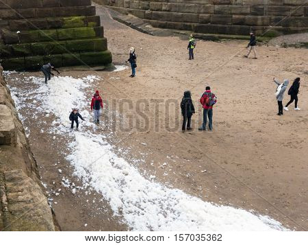 WHITBY ENGLAND - NOVEMBER 5: Adults and children investigating sea foam Whitby beach. In Whitby North Yorkshire England. On 5th November 2016.