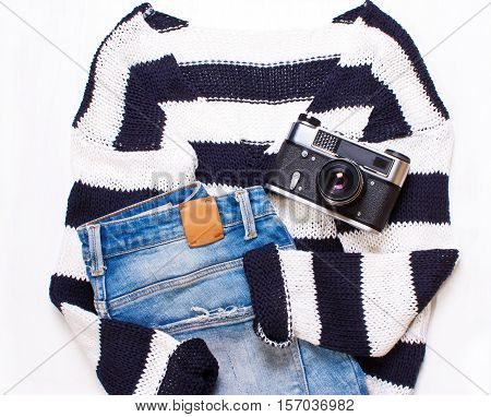 Sweater in white and blue stripes jeans and a camera. Top view flat.fashionable women's casual clothes on a white background. Trendy hipster look set