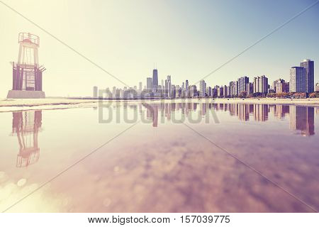 Retro toned sunrise in Chicago city skyline reflected in a puddle USA.