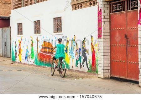 Girl Passing Painted Wall In Turpan, China