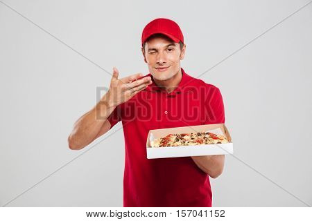 Smiling delivery man with pizza. isolated gray background