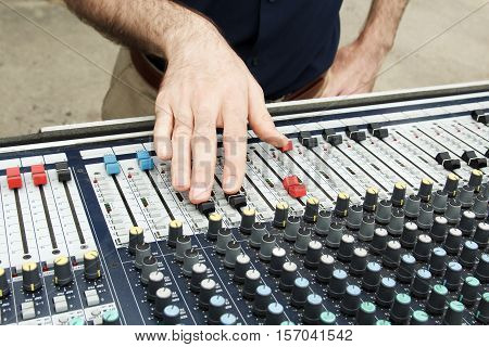 Soundman's palm and microphone on sound mixer background. Music instruments or dj concept. Musical equipment microphone with control console.