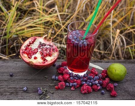 A glass of pomegranate juice with fresh pomegranate fruits on wooden table. Vitamins and minerals. Healthy drink concept.