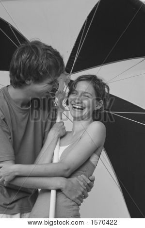 A man and woman laughing under an umbrella a couple in love poster