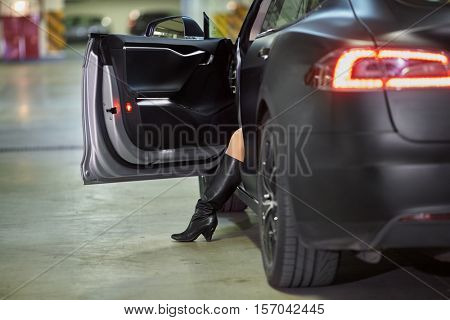 Rear view of modern car with open driver door and leg of woman comes out.