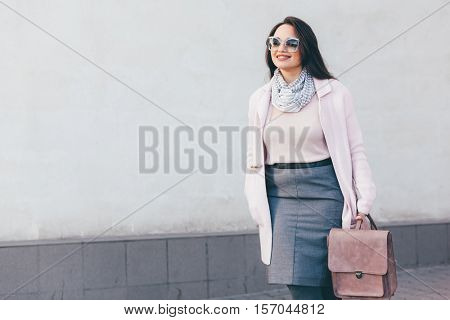 Young stylish woman wearing pink warm coat, skirt and handbag walking in the city street in cold season. Winter fashion, elegant look, outfit in pastel colors. Plus size model.