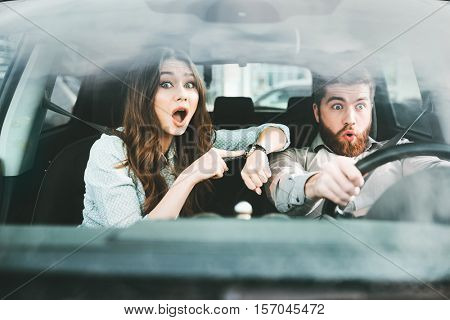 Surprised couple in car. girl shows at wristwatch