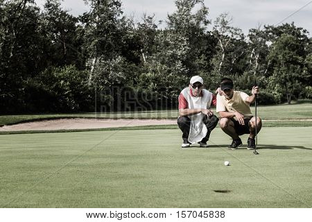 Golfer and caddy reading green, toned image