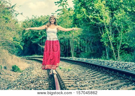 Young lady in red dress walking on railway tracks - retro style