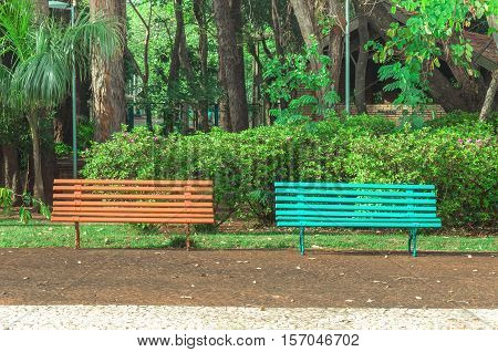 Two benches side by side on a square with trees and a beautiful green vegetation background. Orange and blue bench very peaceful place to sit and relax with friends choose one.