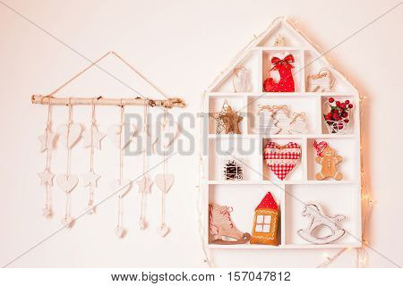 Wooden shelves in shape of cozy home with Christmas decorations poster