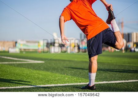 Male players run stretching leg muscles ready for action in a football stadium in the summer outdoors. Male athlete plants the lower body of the foot to stretch your legs get ready for a warm heart.