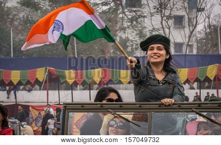 KOLKATA, INDIA - JANUARY 31, 2016: Girl proudly waves the Indian tri-color at the Statesman Vintage Car rally at the Fort William, Kolkata.
