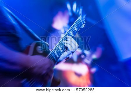 musician playing an electric guitar under blue stage lighting
