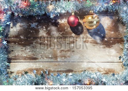 close up view of christmas tree toys and garland on wooden back