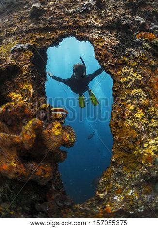 Free diver exploring the ship wreck in a tropical sea