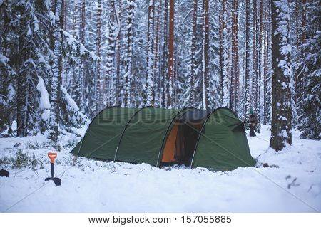 A process of camping in winter forest, setting a tent covered in snow, making a bonfire campfire and cooking food with portable gas cooker and fire, snowy landscape
