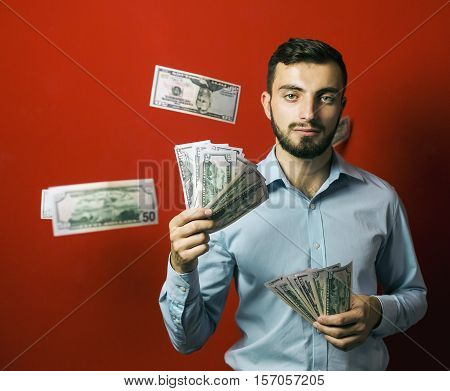 Attractive man with falling dollars banknotes red background, jackpot concept