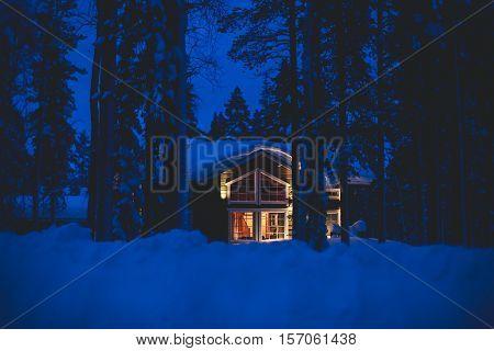 Beautiful scandinavian Finnish swedish norwegian wooden cottage cabin near slopes on a ski resort in the night time
