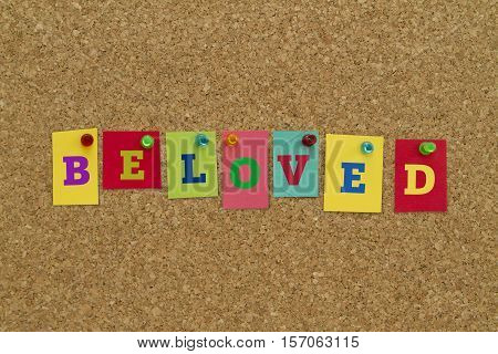 Beloved word written on colorful sticky notes pinned on cork board.