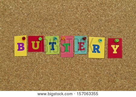 Buttery word written on colorful sticky notes pinned on cork board.