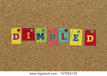Dimpled word written on colorful sticky notes pinned on cork board.