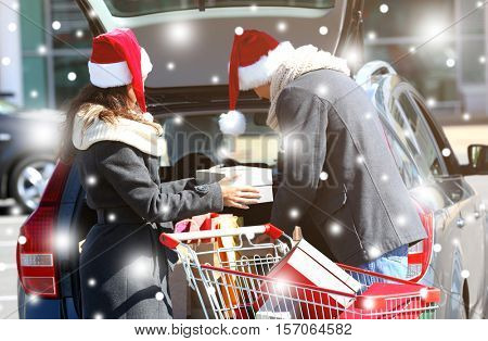 Young couple loading Christmas purchases into car trunk on shopping mall parking. Snowy effect. Christmas shopping concept.
